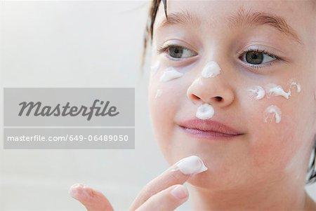Girl rubbing moisturizer on her face