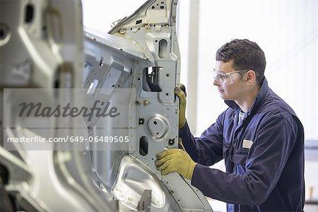 Apprentice working in car factory