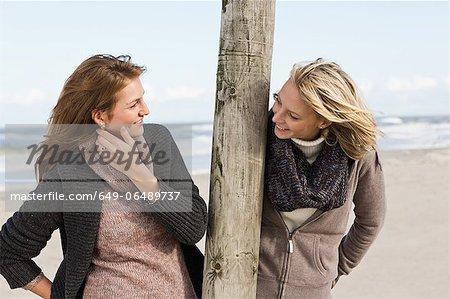 Smiling women talking on beach