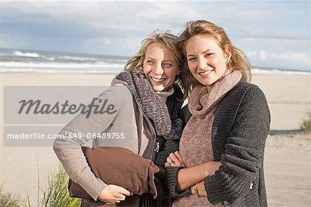 Smiling women standing on beach
