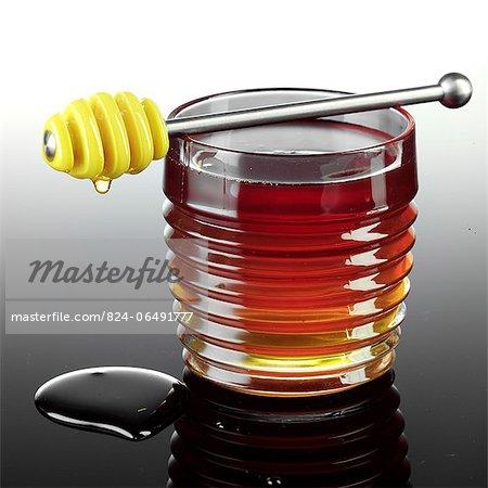 Honey Dipper Resting on a Jar of Honey