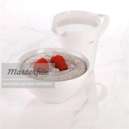 Bowl of Porridge with Raspberries and a jug of Milk