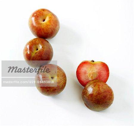 Fresh Whole Loquat Fruit; One Halved; White Background