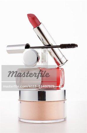 Lipstick, mascara and fingernail polish stacked on moisturizer jar