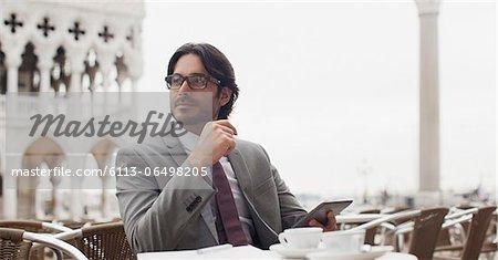 Smiling businessman using digital tablet at sidewalk cafe
