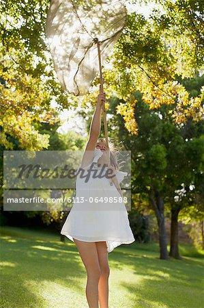 Girl in dress holding butterfly net overhead