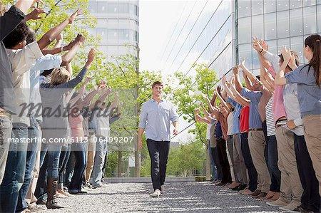 Man walking between cheering crowd