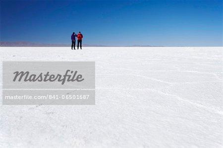 Couple taking photos on Salar de Uyuni (Salt Flats of Uyuni), Potosi Department, Bolivia, South America
