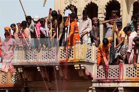 Young men celebrating Holi festival by splashing colored fluids on temple visitors, Nandgaon, Uttar Pradesh, India, Asia