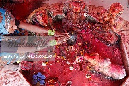 Hindu woman worshipping a lingam during Holi celebration in Goverdan, Uttar Pradesh, India, Asia