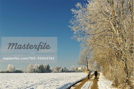 Two People Walking on Road Through Snow Covered Farm Field in Winter, near Villingen-Schwenningen, Baden-Wuerttemberg, Germany
