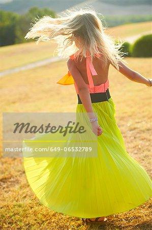 Girl spinning in skirt in field