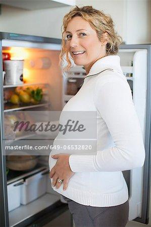 Pregnant woman standing at fridge