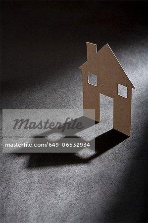 Cardboard house shape casting shadow