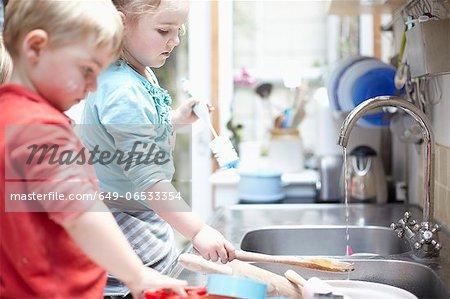 Children washing dishes together