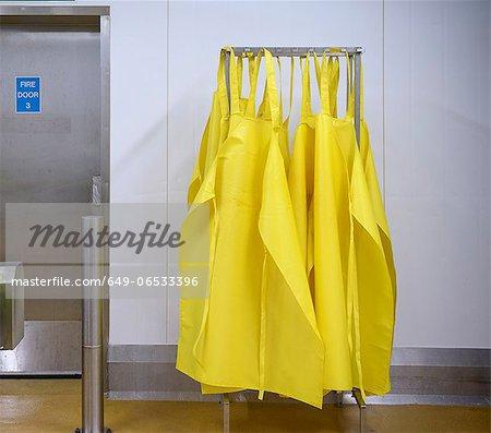 Yellow aprons on drying rack