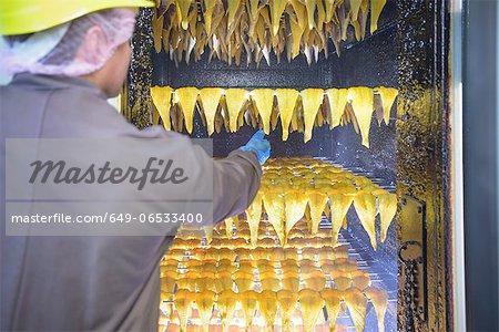 Worker smoking haddock filets in factory