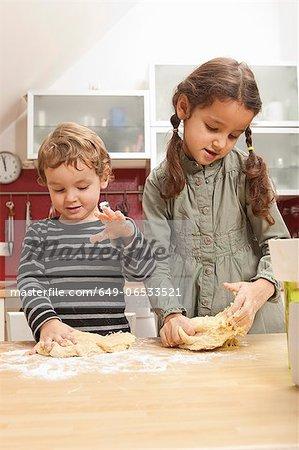 Children kneading dough in kitchen