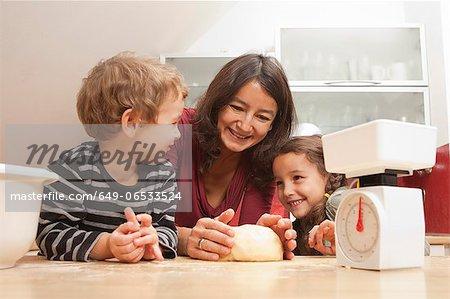 Mother and children baking in kitchen
