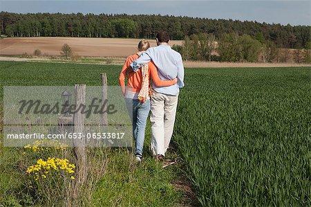 A couple walking side by side in a field, rear view