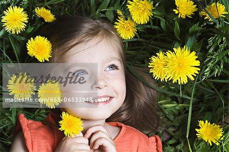 A young girl lying amongst dandelions
