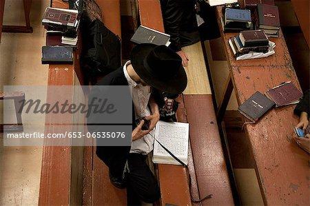Jewish man holding tefillin  in synagogue