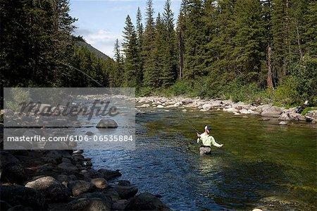 Man fly fishing in mountain stream.