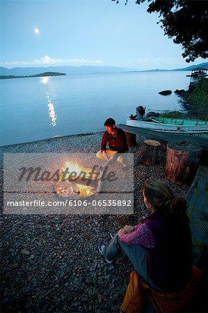 Man and woman by campfire at night on lake shore.