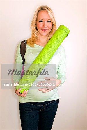 A pregnant women holding a yoga mat inside.