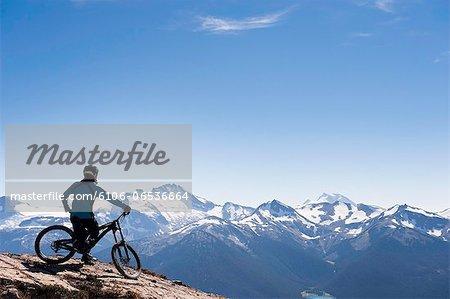 mountain biker resting on alpine trail