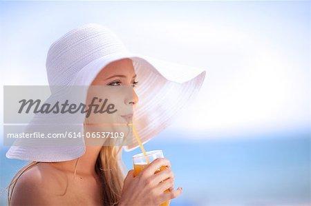 Woman in floppy hat drinking juice