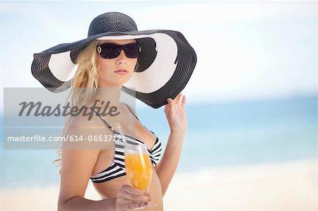 Woman in bikini and floppy hat on beach