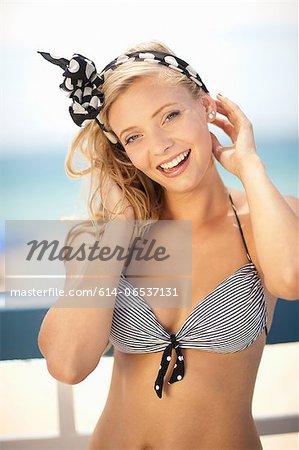 Smiling woman tying scarf in hair
