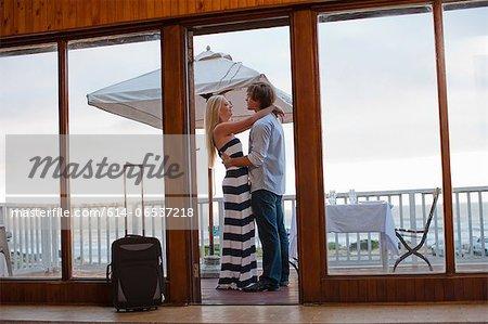Couple hugging on beachfront patio
