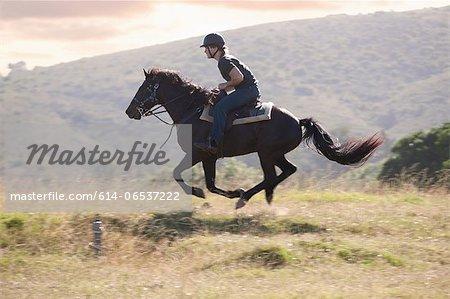 Man riding horse in rural landscape