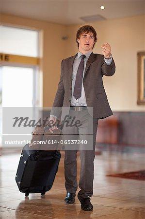 Businessman rolling luggage in lobby