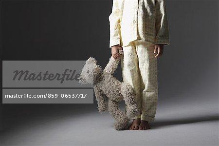 Girl in a pajama holding a teddy bear