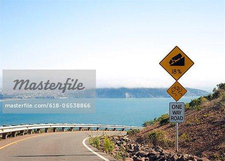 Winding steep road along coast with warning signs