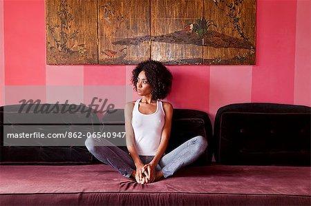 Brazil, Rio de Janeiro city, Gavea, La Maison Hotel, model in jeans and a white vest top relaxing on a velvet sofa in the La Maison boutique hotel MR PR