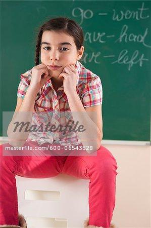 Portrait of Girl Sitting in Front of Chalkboard in Classroom