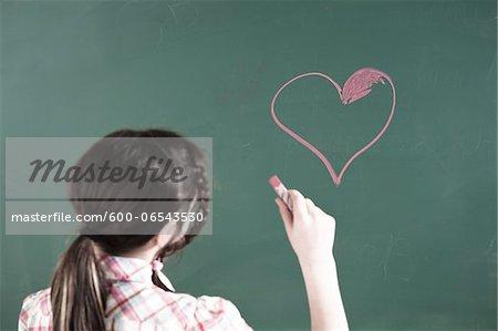 Girl Drawing Heart on Chalkboard in Classroom