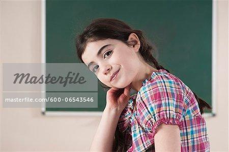 Portrait of Girl in front of Chalkboard in Classroom