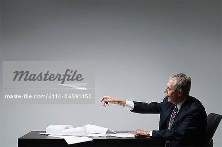 A businessman throwing a paper aeroplane