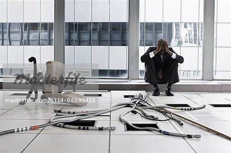 Despairing businessman in abandoned office