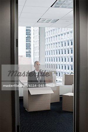 Businessman in cardboard box