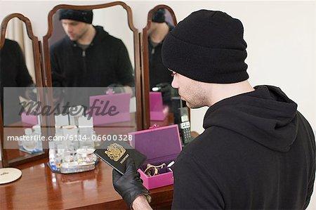 Burglar stealing passport