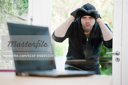 Burglar looking at laptop through window