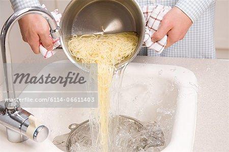 Person draining spaghetti