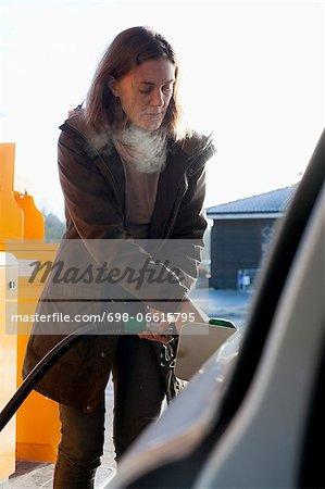 Woman refueling car in winter
