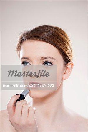Portrait of Teenage Girl Applying Lipstick in Studio Shot on White Background